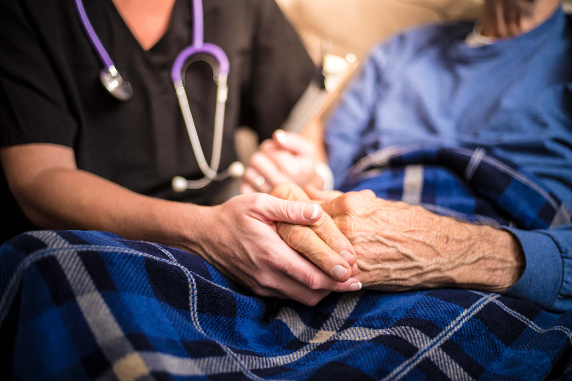 End-of-life care patient holding hands with caregiver at Tore's Home in Brevard, NC